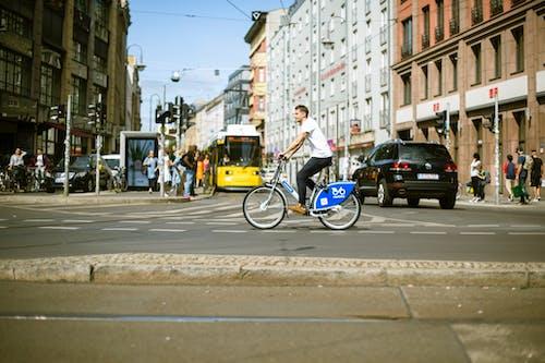 A Man in White Shirt Biking in the City
