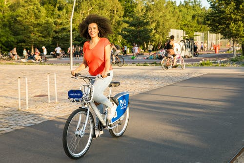 A Curly-Haired Woman Riding a Bike while Looking at Camera