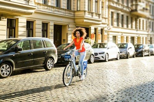 A Curly-Haired Woman in Orange Shirt Biking
