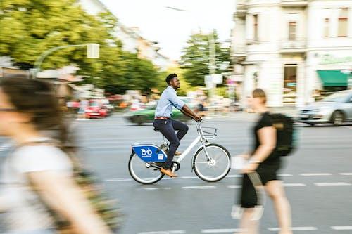 A Man in Casual Wear Biking in the City