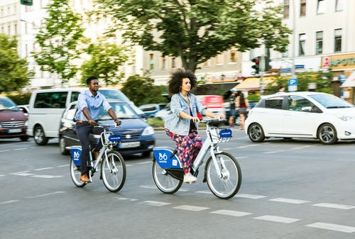 A Man and Woman in Casual Wear Biking in the City