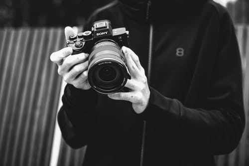 Grayscale Photo of a Person Holding Sony DSLR Camera