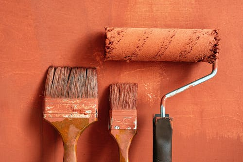 Close-Up Shot of Variety of Paintbrushes with Brown Paint
