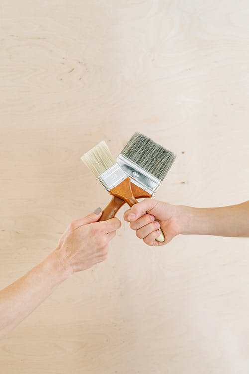 Close-Up Shot of Two People Holding Paintbrushes