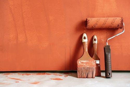 Close-Up Shot of Variety of Paintbrushes with Orange Paint