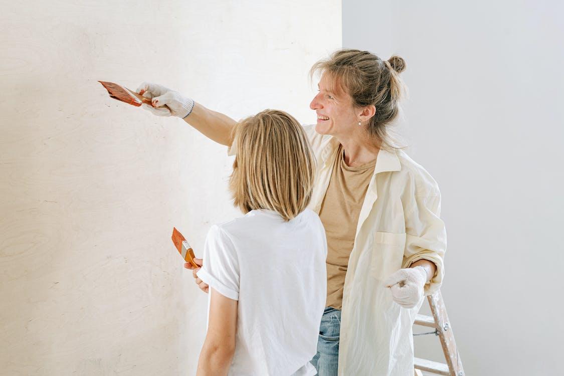 Woman in White Long Sleeve Shirt Holding Orange Paint Brush