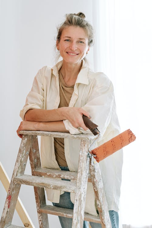A Woman Looking at Camera while Holding a Paint Roller