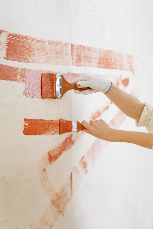 Close-Up Shot of Two People Painting the Wall Brown