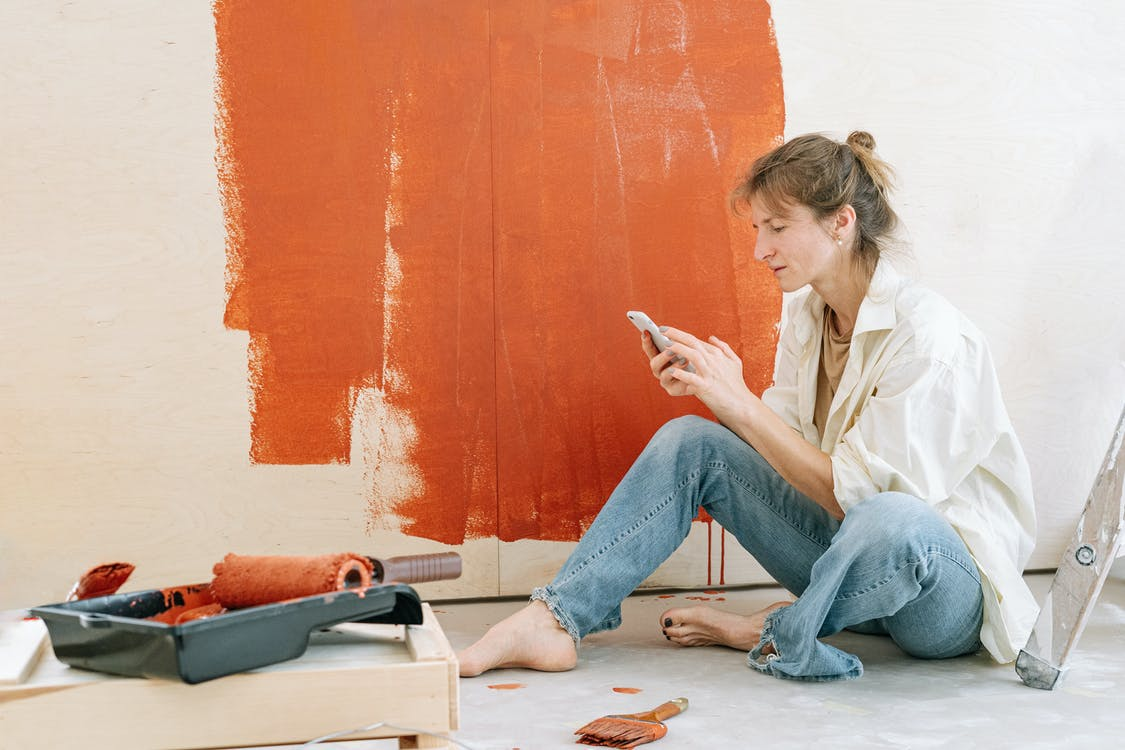 Woman in Blue Denim Jeans Sitting on White Table