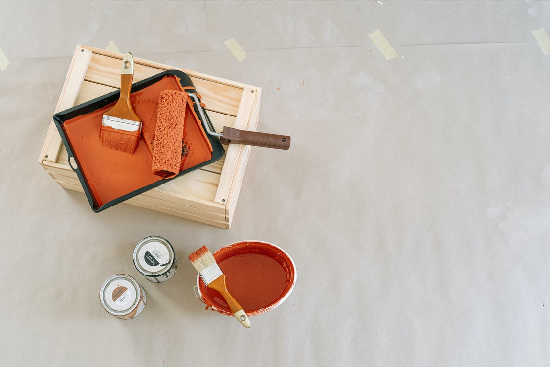 Brown Leather Sling Bag on Orange Plastic Container