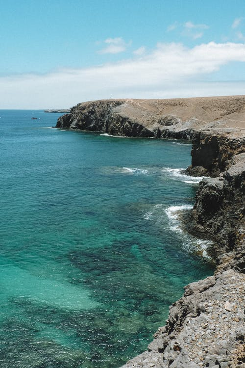 Rocky cliff near calm sea water