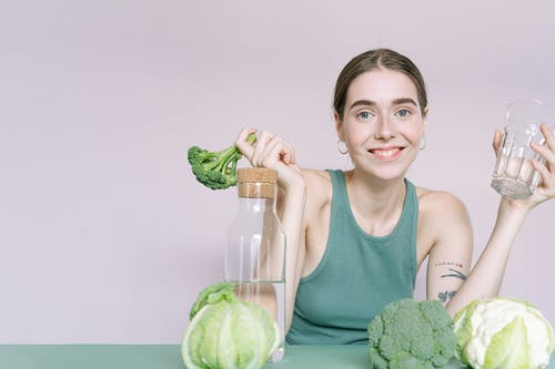 Woman in Green Tank Top Holding Green Cabbage