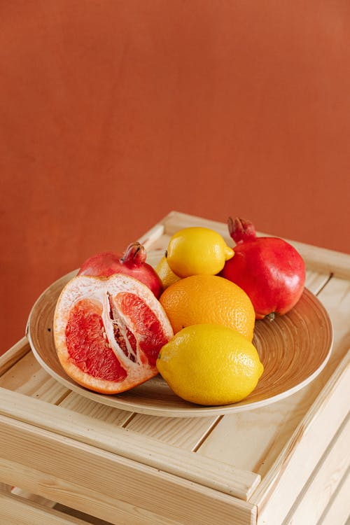 Red And Yellow Citrus Fruits on Brown Wooden Board