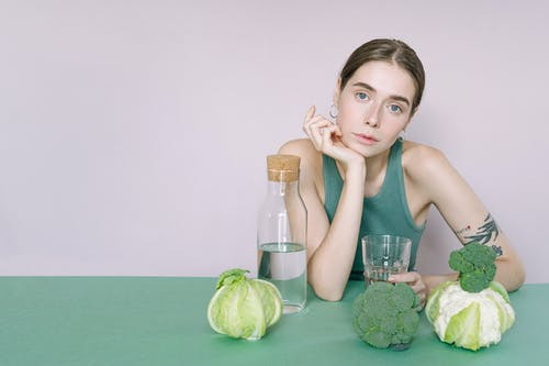 Woman in Gray Tank Top Sitting on Green Table