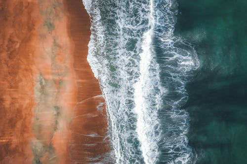 Aerial view of turquoise ocean with waves and foam on sandy beach in summer
