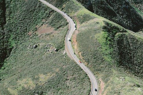 Asphalt highway with cars along peak of green hills