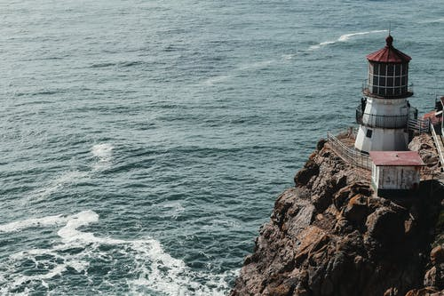 From above of small shabby beacon on top of rocky cliff with waving ocean below