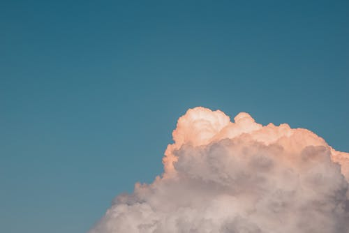 Minimalist landscape of fluffy cloud colored in sunset light floating in blue sky