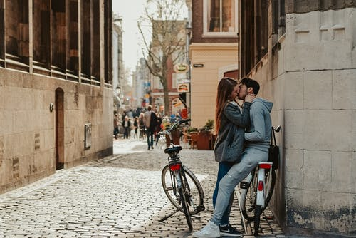 Romantic couple with bicycles kissing on old street