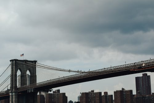 Low angle of Brooklyn bridge with waving American flag against high rise buildings and gloomy clouds