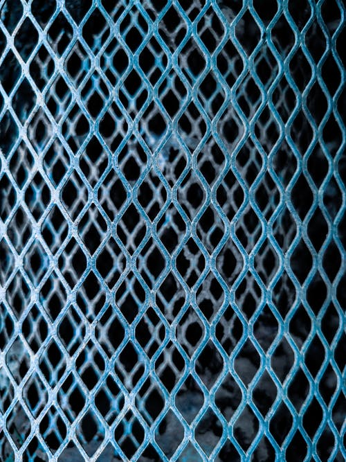 Background of folded metal net with metal grid in shape of rhomb on dark background