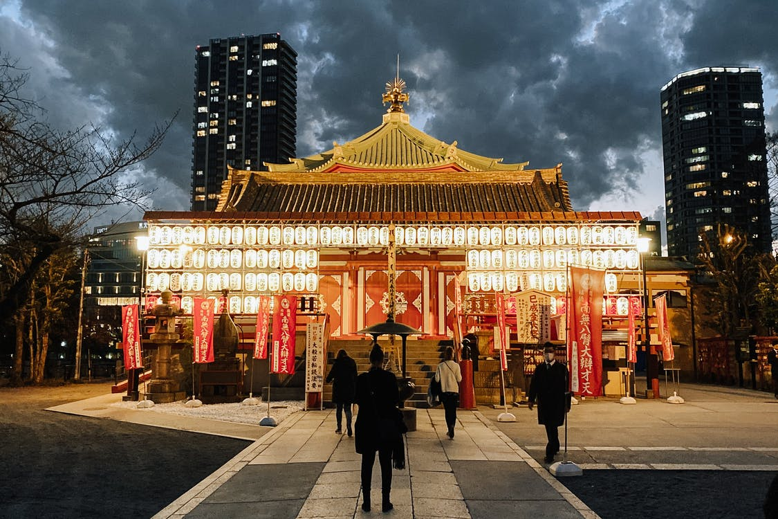 Glowing facade of Bentendo Temple with glowing lanterns against skyscrapers in Ueno Park of Tokyo