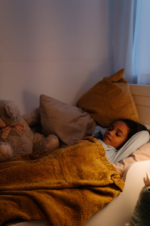 A Young Girl Resting on Her Bed