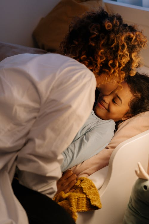 A Mother Kissing Her Daughter Before Sleeping