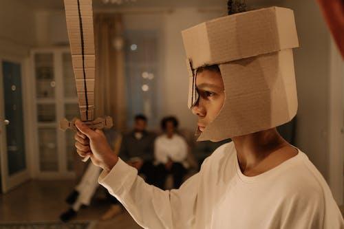 Boy in White Long Sleeve Shirt Holding Brown Cardboard Sword