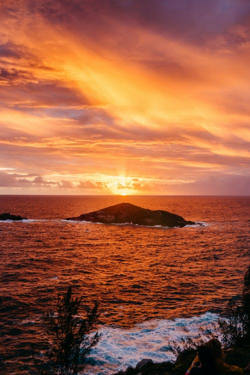 Magnificent scenery of rocky formations in rippling ocean with foamy waves crashing near coast against picturesque colorful sunset sky in Arraial do Cabo
