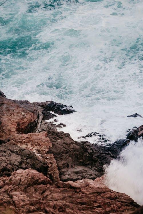 Powerful foamy sea waves washing rocky cliff
