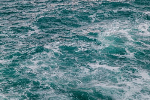 High angle of foamy waves of powerful turquoise ocean with uneven surface in sunlight