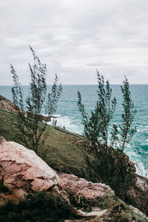 Rocky hill slope covered with green moss near powerful turquoise ocean with foamy waves against cloudy sky