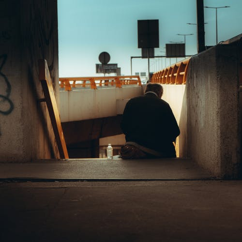 Man in Black Jacket Sitting on Concrete Stairs