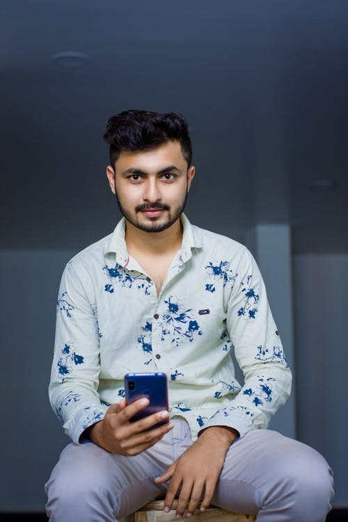 Boy in White and Blue Floral Button Up Long Sleeve Shirt Holding Blue Smartphone