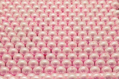 Pink and White Beads on Pink Textile
