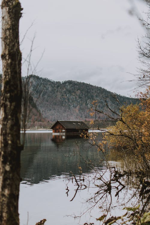 Calm lake with submerged house in mountainous valley
