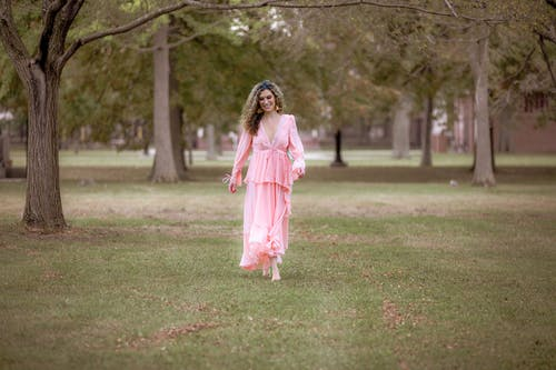 Cheerful female in stylish dress standing on green grass in park