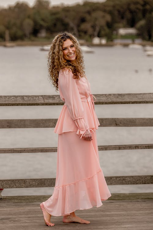 Full body of positive woman with long curly hair in stylish dress standing on boardwalk near lake and looking at camera in daytime