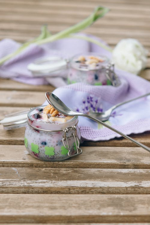 Stainless Steel Spoon on White and Green Floral Ceramic Jar