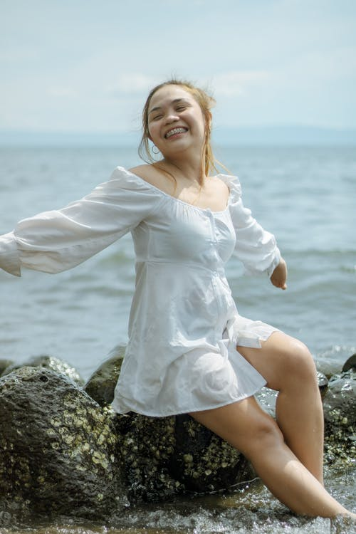 Cheerful young Asian female in white dress enjoying sun and sea water while sitting on rocks with hands sideways