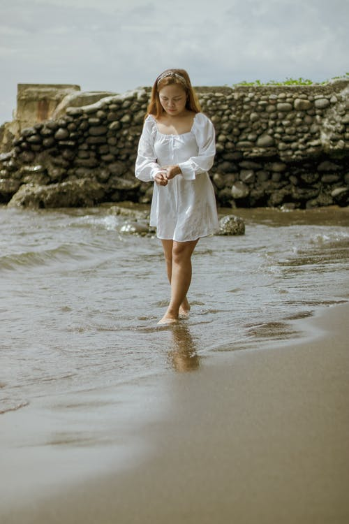 Young woman on wet sandy shore