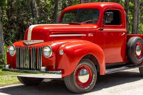 Red Vintage Car Parked on Gray Asphalt Road