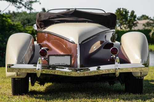 Vintage Brown and White Car on Green Grass Field