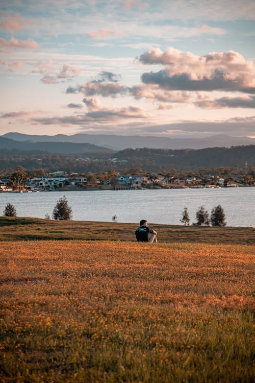 Man in Black Jacket Sitting on Grass Field Near Body of Water