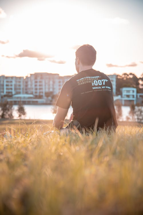 Man in Black Crew Neck T-shirt Sitting on Green Grass Field