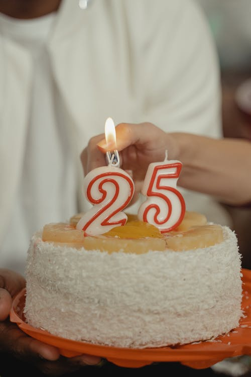 Person Holding Cake with Candles for 25th Birthday
