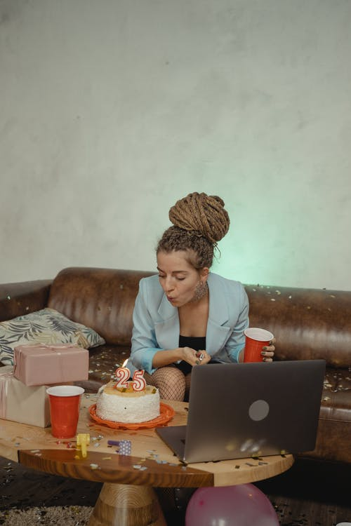 Woman in White Shirt Sitting on Couch Using Macbook
