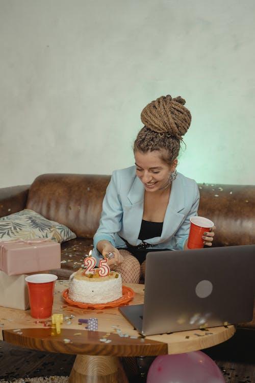 Woman in Gray Blazer Sitting on Brown Sofa Using Macbook