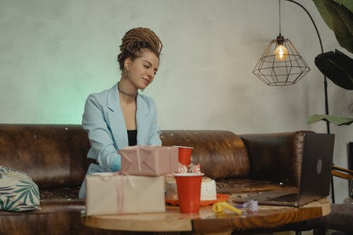 Woman in White Blazer Sitting on Brown Wooden Chair